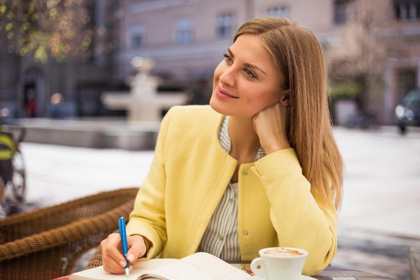 Eine junge Frau mit langen blonden Haaren, sitzt in einem Restaurant und schaut verträumt in den Himmel. Sie macht einen zufriedenen Eindruck, weil Sie ihr Selbstbewusstsein mit dem Programm der unibee Institute gut entwickeln konnte. Sie ist bekleidet mit einer gelben Sommerjacke und einer weiss/grau gestreiften Bluse. In der Hand hält sie einen Blauen Stift und schreibt damit etwas in den Terminkalender. Der Hintergrund ist nur verschwommen zu sehen, damit die Frau im deutlichen Fokus des Bildes steht.