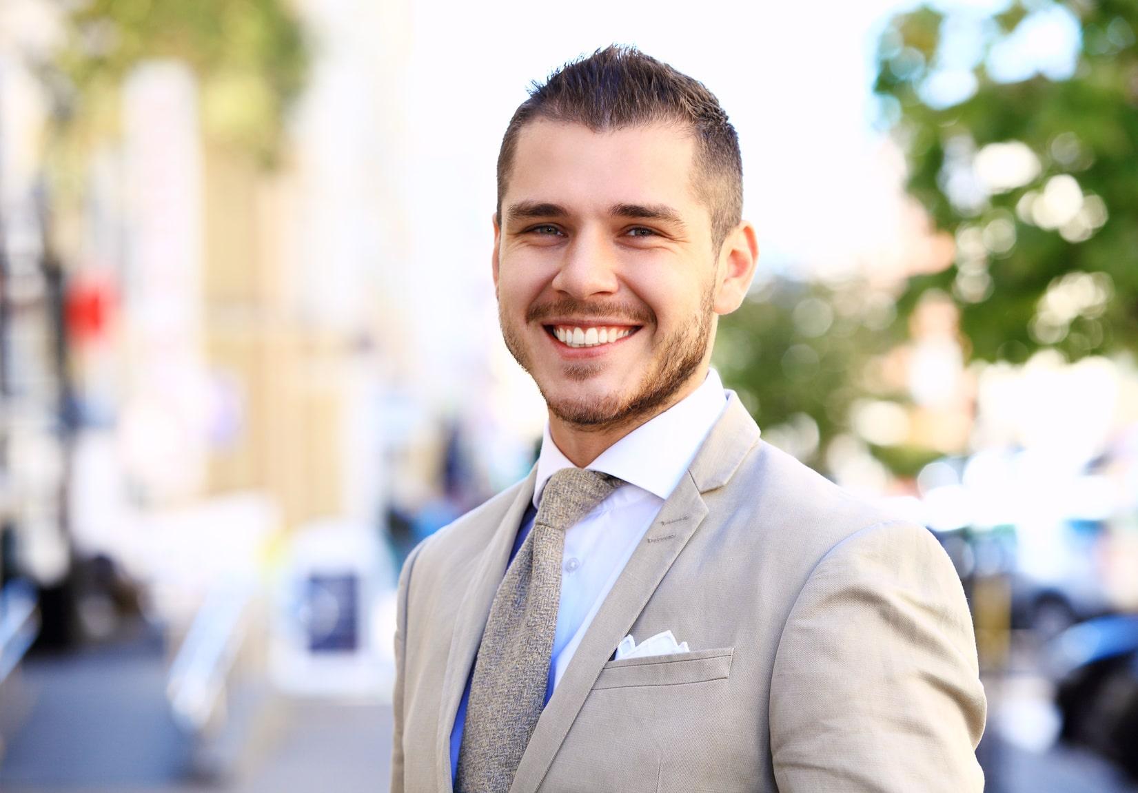 Ein junger Mann in einem grauen Anzug lächelt Selbstbewusst, weil das Programm der unibee Institute zum Selbstvertrauen aufbauen, schnell und gut geholfen hat.