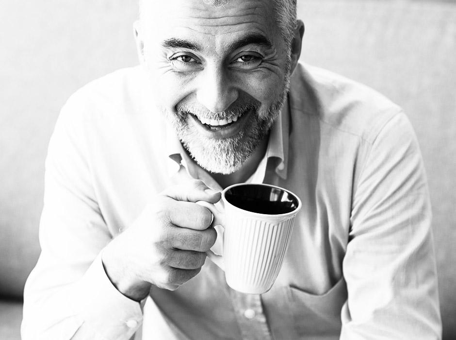 Ein älterer Mann lächelt voller Genuss in die Kamera und strahlt damit vollste Zufriedenheit und Selbstvertrauen aus. In der Hand höät er eine Tasse Tee und er trägt ein weisses Hemd. Der Hintergrund ist neutral weiss. Der Mann hat kurze graue Haare und trägt einen 3 Tage Bart.