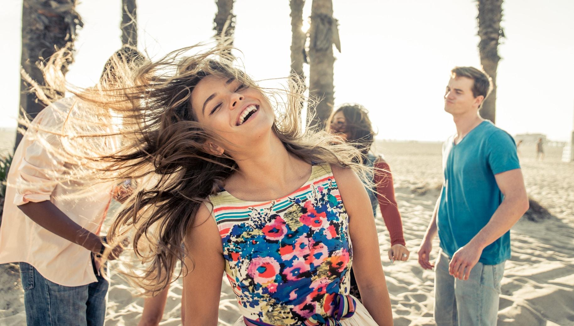 Eine junge Frau in einem Sommerkleid mit bunten Blumen darauf, steht an einem Strand mit Palmen und lacht sehr glücklich. Sie macht einen sehr selbstbewusstsen Eindruck. Sie hat lange braune Haare, welche im Wind wehen. Im Hintergrund sind 3 weitere Personen zu sehen, welche locker tanzen.