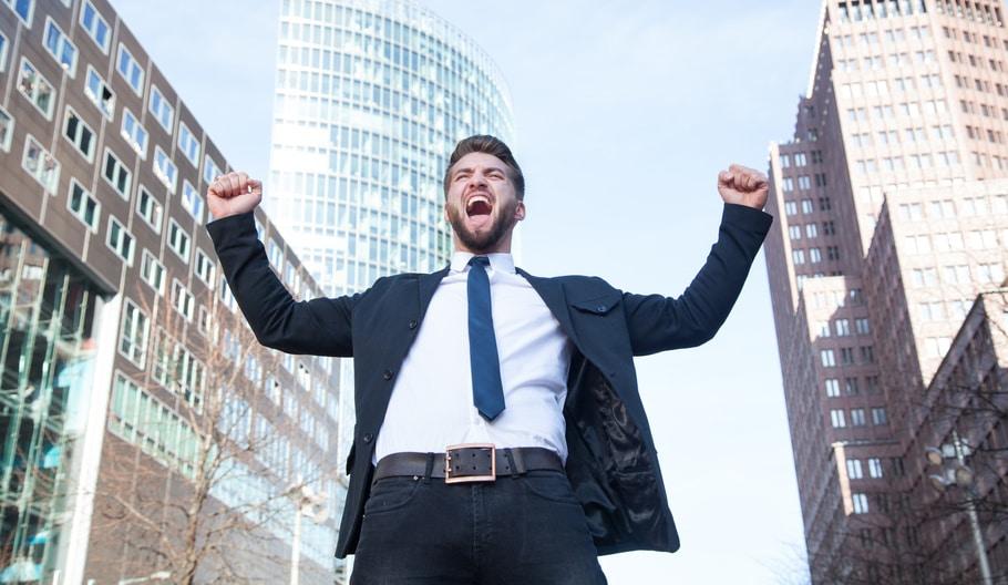 Ein Mann steht auf einer Strasse und ist bekleidet mit einem blauen Anzug und blauer Kravatte. Er hebt beide Arme nach oben und ballt seine Hände zu einer Faust. Mit seiner Gestik und Mimik drückt er aus, dass er mit dem Programm der unibee Institute, ein gutes Selbstbewusstsein erreicht hat. Er hat braune nach hinten gekämmte Haare und trägt einen Vollbart. Im Hintergrund ist die Frankfurter Skyline zu sehen.