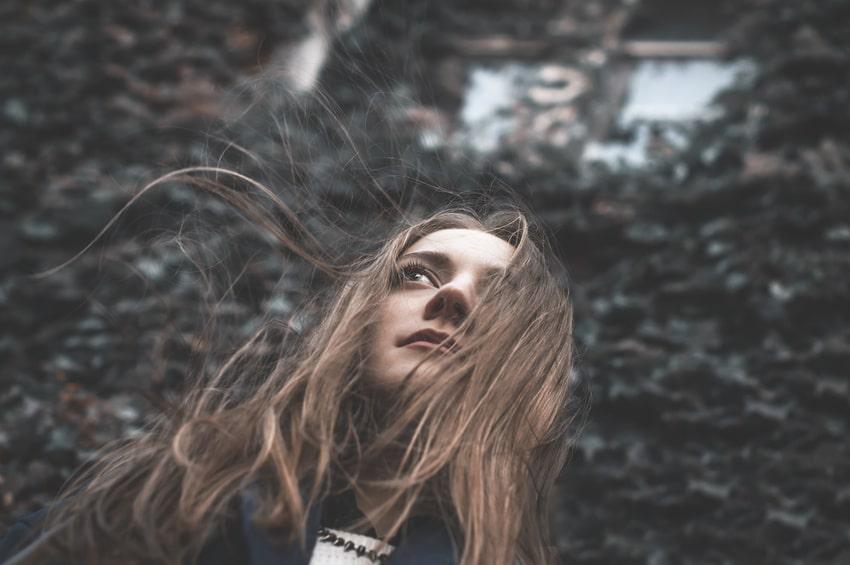 Eine junge Frau steht in einer einsamen Landschaft und die langen blonden Haare wehen im Wind. Ihr Gesichtsausdruck ist sehr Selbstbewusst und freundlich. Sie ist bekleidet mit einer dunkelblauen Windjacke und weissem Pullover.