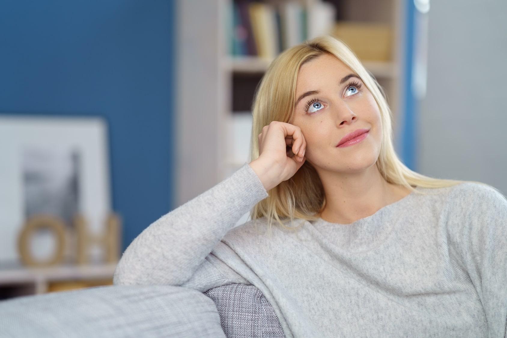 Eine Frau sitzt auf einem Sofa und schaut nach oben. Sie ihrer Mimik zeigt sie deutlich, dass sie mit dem Programm der unibee Institute, ihr Selbstbewusstsein stärken konnte und jetzt in einer guten Balance sich wohl fühlt. Sie hat glatte, lange, blonde Haare und ist bekleidet mit einem hellgrauen Pullover. Im Hintergrund ist verschwommen ein Wohnzimmer zu sehen, welches eine blaue Farbe an der Wand hat.