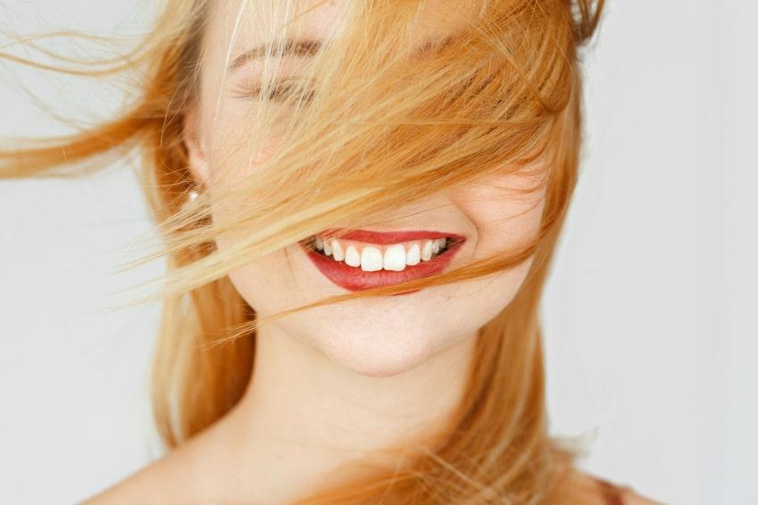 Ein lachendes Gesicht einer hübschen jungen Frau, strahlt starkes Selbstbewusstsein aus. Ihre langen hellblonden Haare wehen Ihr ins Gesicht, sodass das linke Auge nicht zu erkennen ist. Der Hintergrund ist schlicht weiss.