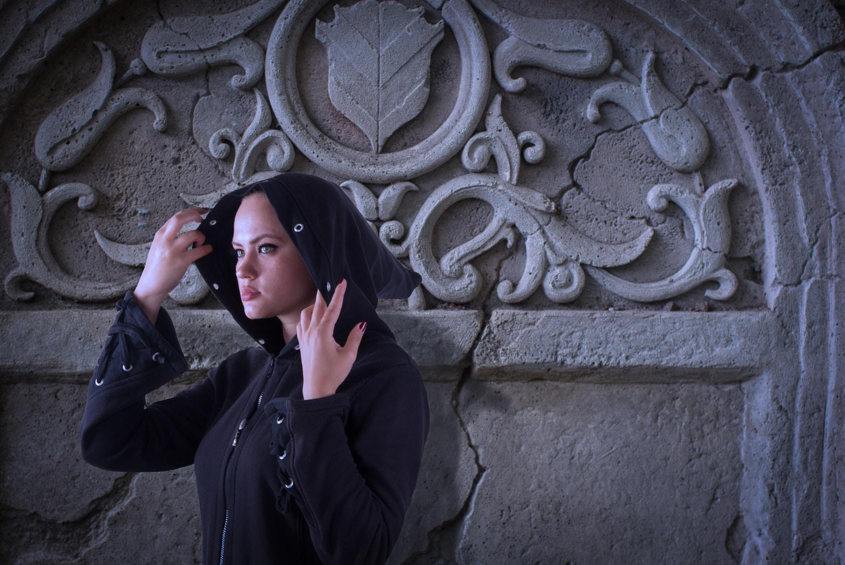 Eine junge Frau steht vor einer Klostermauer und hebt ihre Kaputze mit beiden Händen hoch. Durch den Aufenthalt in einem Kloster und den Ausdruck ihrer Gesichtsmimik hat sie deutlich mehr Selbstbewusstsein bekommen. Sie ist bekleidet mit einer schwarzen Kaputzenjacke.