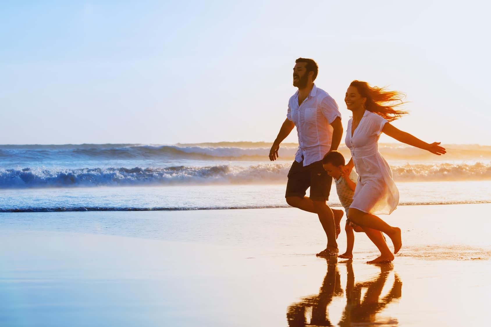 Ein Mann, eine Frau und ein Kind laufen an einem eisamen Strand entlang und machen einen sehr glücklichen Eindruck. Das Programm der unibee Institute hat stark geholgen, dass die Familie das Selbstbewusstsein stärken konnte und somit alle in eine positive Zukunft blicken. Der Mann ist bekleidet mit einem weissen Freizeithemd, kurzer schwarzer Hose und Sandalen. Die Frau trägt ein weisses Sommerkleid das im Wind weht. Das Kind rägt ein grünes T-schirt. Im Hintergrund ist das Meer mit einem roten Sonnenuntergang zu sehen.