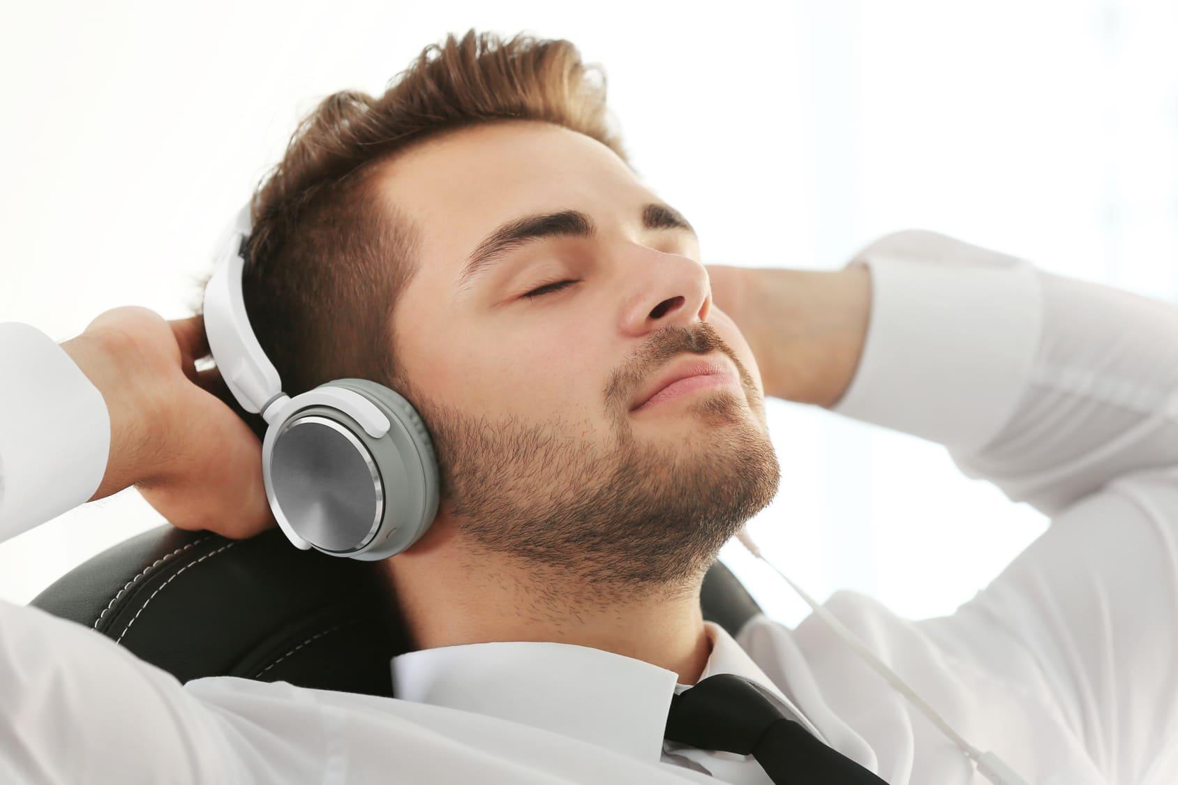 Ein junger Mann liegt auf einem Sofa und hat die Augen geschlossen. Er hat große Kopfhörer auf den Ohren und hört sich eine Hypnose CD Selbstbewusstsein stärken an. Er lächelt leicht und hat die Arme hinter seinem Kopf verschränkt. Bekleidet ist er mit einem weissen Hemd und einer schwarzen Kravatte. Der Hintergrund ist glanz weiss.