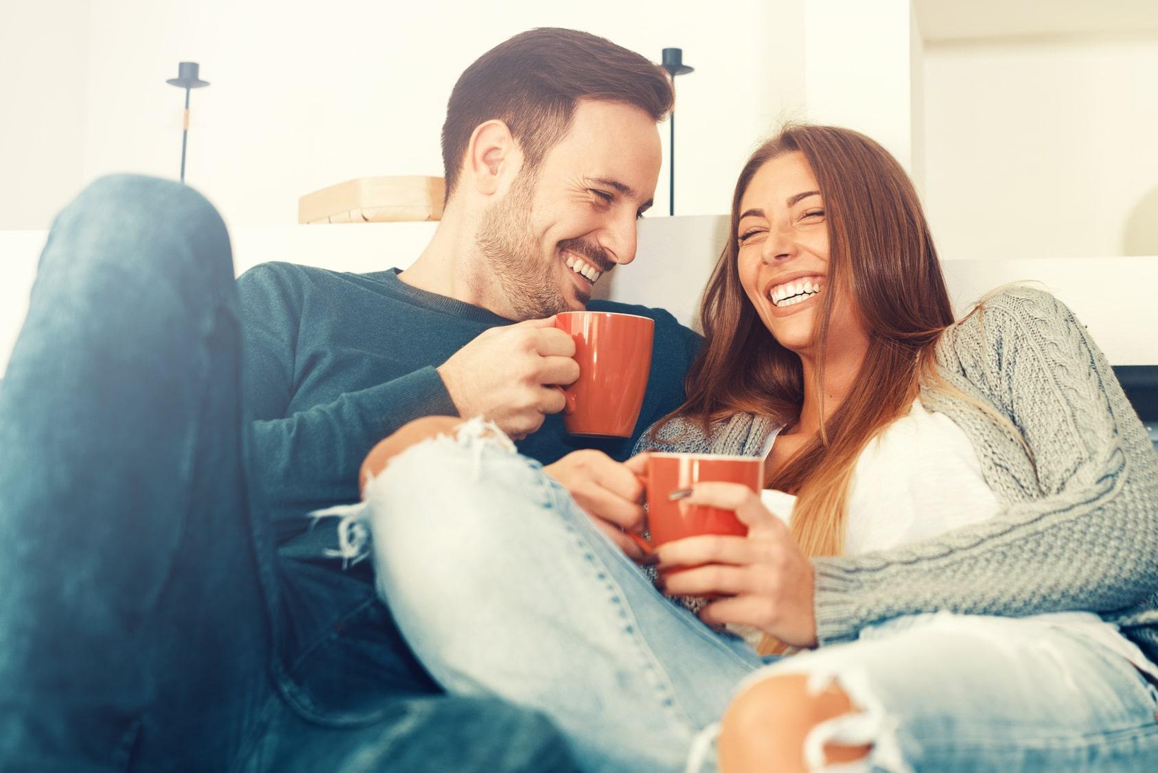 Ein junges Paar sitzt in einem Sofa und lacht Herzhaft zusammen. Beide halten dabei eine rote Tasse Tee in der Hand. Beide machen einen sehr Selbstbewusstsein Eindruck und freuen sich, dass das Programm der unibee Institute geholfen hat, eine gute Balance im Leben zu bekommen. Der Mann hat kurze braune Haare und die Frau hat sehr lange braune Haare. Im Hintergrund ist ein Wohnzimmer mit weissen Möbeln zu sehen.