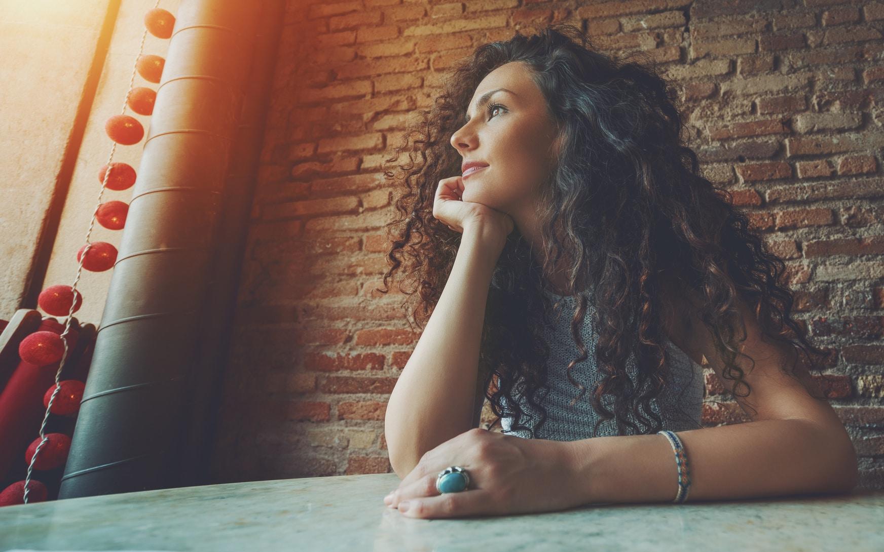 Eine Frau mittleren Alters sitzt an einem Tisch und schaut sehr Selbstbewusst in die Ferne. Sie hat sehr lange, gelockte schwarte Haare und ist bekleidet mit einem hellblauen, trägerlosem Shirt. Im Hintergrund ist eine Natursteinmauer zu sehen.