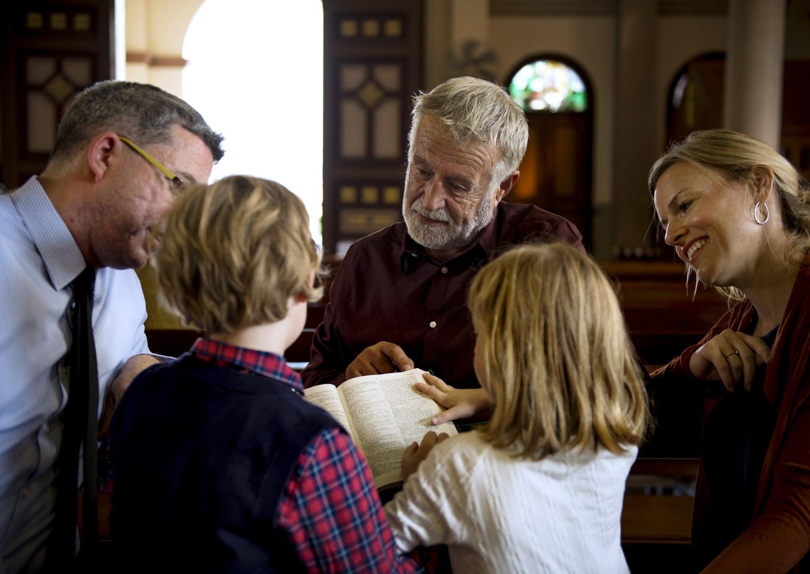 Eine Familie mit 2 Kindern unterhält sich in einer Kirche mit einem Pastor. Alle schaue freundlich und lesen dabei in einer Bibel. Die Eltern führen die Kinder in die gepflogenheiten ein und stärken damit signifikant das Selbstbewusstsein.