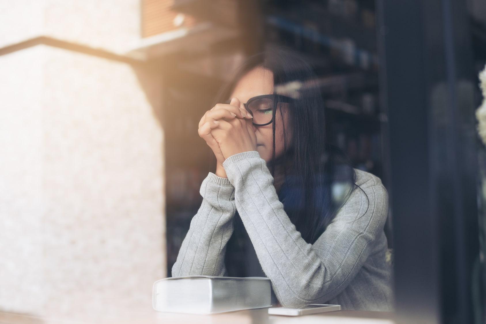 Eine junge Frau mit langen schwarzen Haaren und schwarzer Brille, sitzt hinter einer Glasscheibe und hat ihre Hände zum Gebet gefaltet. Dabei hat sie Ihre Augen geschlossen und eine Bibel liegt vor ihr auf dem Tisch. Sie zeigt mit dieser Gestik, dass sie mit ihrem Glauben, das Selbstbewusstsein aufbauen tut.