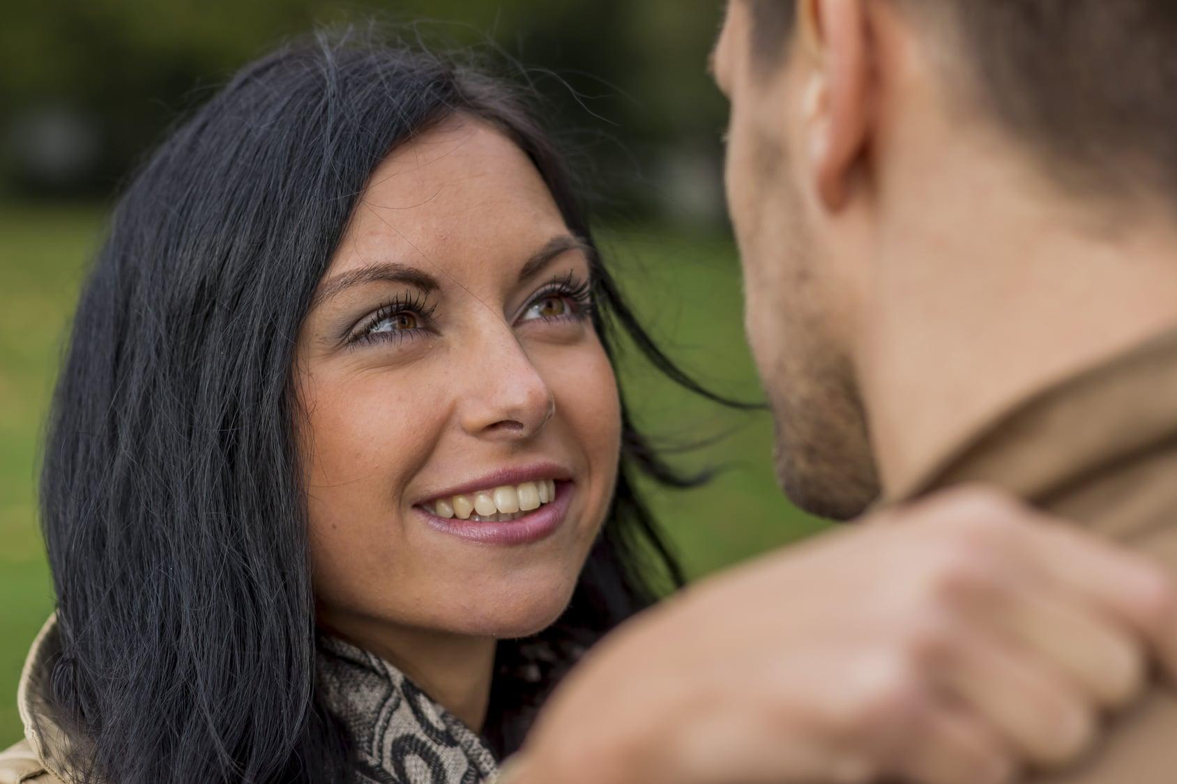 Eine Frau mittleren Altes umarmt ihren Freund und lächelt ihm in die Augen. Ihre Mimik strahlt ein gutes Selbstbewusstsein aus. Sie hat Schulterlange schwarze Haare und grüne Augen. Sie ist bekleidet mit einer braunen Jacke und einen schwarz/braunen Schaal. Im Hintergrund ist eine grüne Wiese zu sehen.
