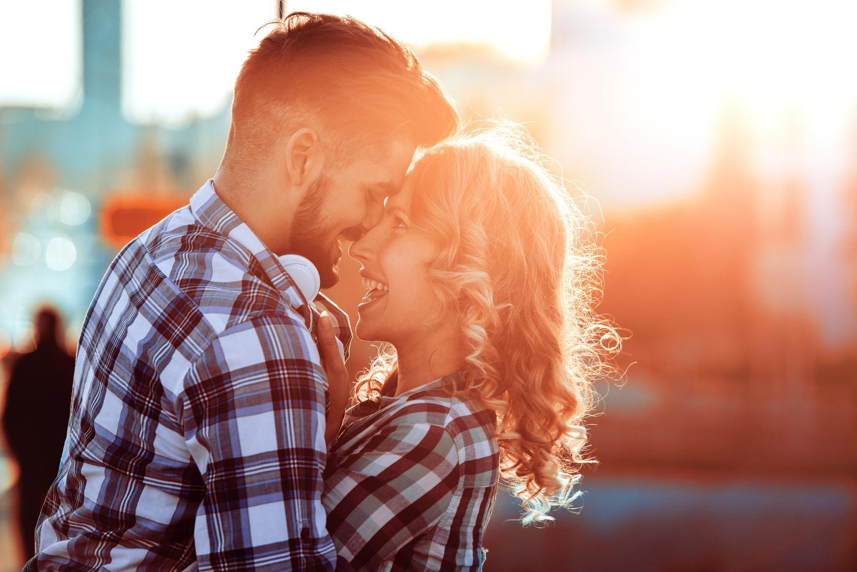 Ein Liebespaar trifft sich auf einer Strasse und umarmen sich sehr glücklich. Sie wirken sehr Selbstbewusst, weil beide mit dem Programm der unibee Institute eine gute Lebensbalance erreicht haben. Beide sind bekleidet mit rot, blau, schwarz und weiss karrierten Hemd. Der Mann hat kurze braune Haare und einen 3 Tage Bart und die Frau hat lange gelockte blonde Haare. Im Hintergrund ist ein rötlicher Sonnenuntergang zu sehen.