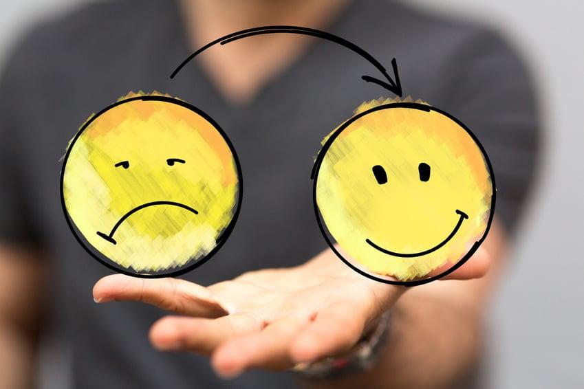 Das Bild zeigt 2 gelbe Smilies an einer Glasscheibe aufgezeichnet. Ein Smilie lacht und der andere Smilie ist traurig. Ein schwarzer Pfeil zeigt von dem traurigen Smilie zu den glücklichen Smilie. Die Aussage dieser Botschaft ist: Stärke das Selbstbewusstsein und sei wieder glücklich.