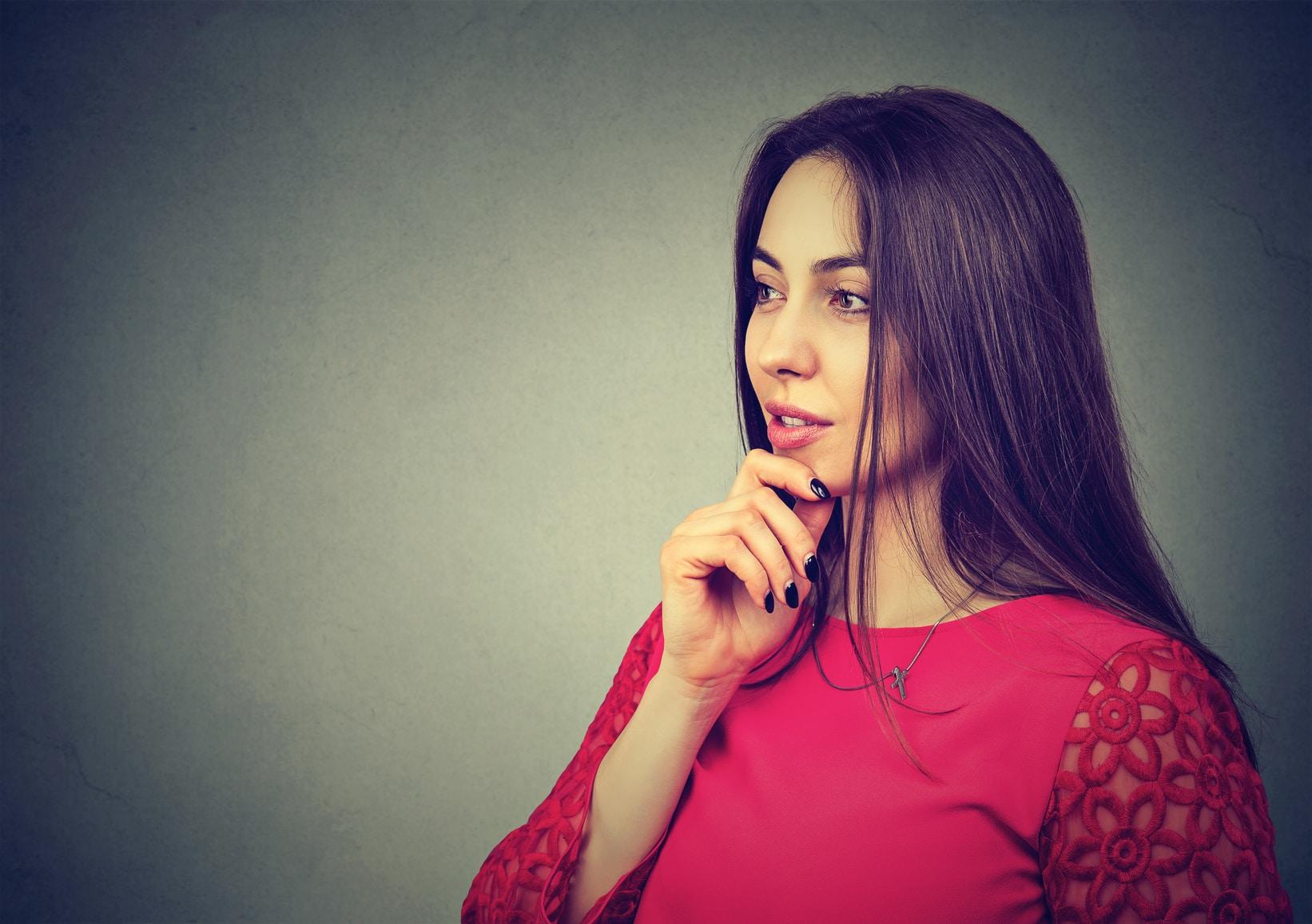 Eine Frau mit langen schwarzen Haaren schaut sehr selbstbewusst in die Ferne. Sie hält dabei ihren rechten Arm unter dem Kopf, denn diese Mimik soll Stärke und Sicherheit in der Gefühlsbalance ausdrücken. Sie ist bekleidet mit einem roten Pullover. Der Hintergrund ist grau.