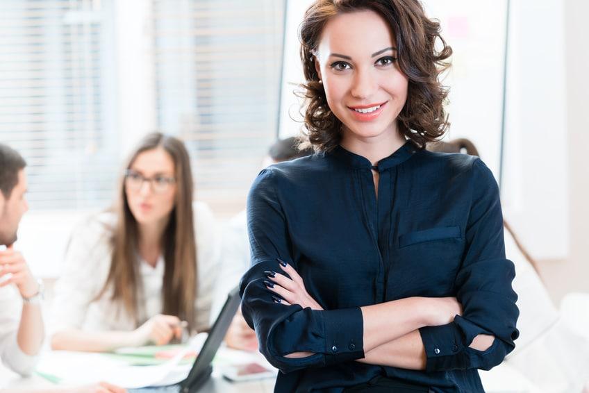 Eine Geschäftsfrau steht mit verschränkten Armen vor einem Schreibtisch. Damit zeigt sie, dass sie mit dem Programm der unibee Institute, ein gutes Selbstbewusstsein gewinnen konnte. Ihr lächeln zeigt eine ausgeglichene und sichere Lebensbalance. Sie ist bekleidet mit einer dunkelblauen Jacke und trägt lockige braune Haare, welche Schulterlang sind. Im Hintergrund sind 3 andere Personen verschwommen zu sehen, weil der Kamerafokus ausschließlich auf die Frau bezogen ist.