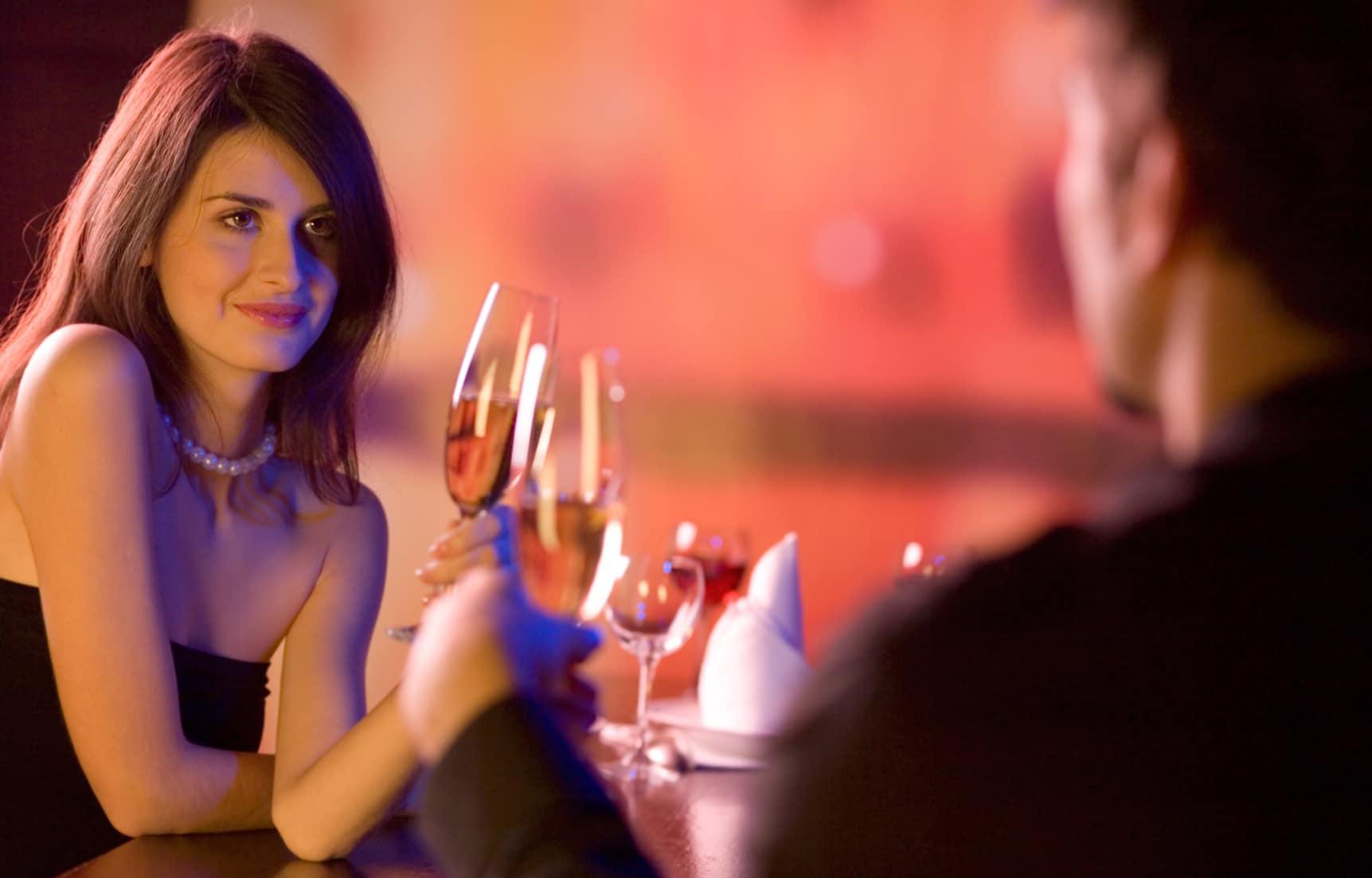 Eine Dame sitzt mit einem Mann in einem Restaurant und beide stossen mit einem Glas Wein an. Sie hat einen sehr ausgeprägten und selbstbewussten Blick. Mit dem Programm der unibee Institute, hat die Frau eine ausgeglichene Wohlfühlbalance bekommen und zeigt diese auch deutlich in der Öffentlichkeit. Die Frau hat lange braune Haare und ist mit einem schwarzen Abendkleid bekleidet. Der Mann ist nur von hinten zu sehen. Der Hintergrund hat ein rötliches Licht und ist verschwommen, da der Kamerafokus ausschließlich auf der Frau liegt.