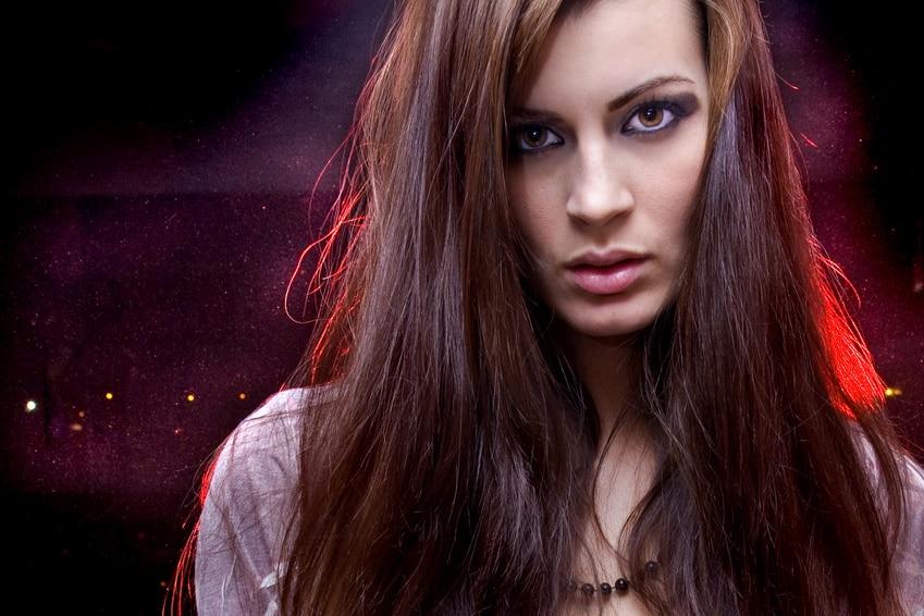 Eine junge Frau sieht mit starren Blick in die Kamera. Sie hat lange dunkelbraune Haare und blau geschminkte Augenlieder. Der Hintergrund ist leuchtend rot. Mit ihrer Mimik drückt sie aus, dass ihr das Programm der unibee Institute gut getan hat und sie ihr Selbstbewusstsein sehr gut aufbauen konnte.