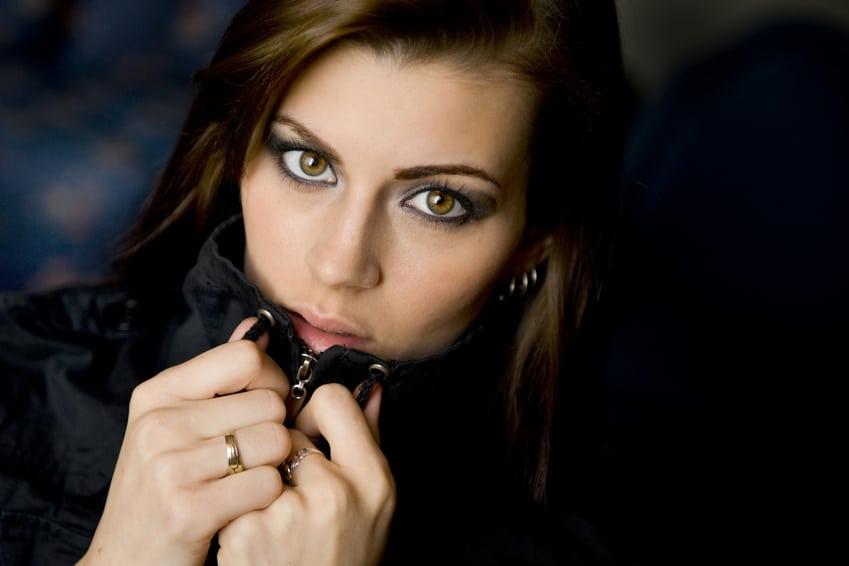 Eine Frau mit langen dunkelbraunen Haaren und grünen Augen zieht Ihre schwarze Lederjacke über Ihr Kinn. In ausdrucksstarker Blick zeigt deutlich, dass sie mit dem Programm der unibee Institute das Selbstbewusstsein erfolgreich aufbaun konnte. Der Hintergrund ist schwarz. Der Bildfokus liegt nur auf den Kopf der Frau.