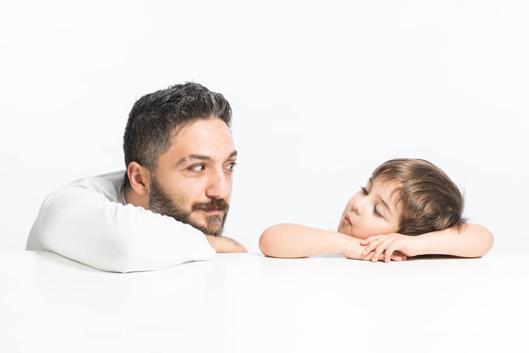 Ein Mann sitzt mit seinem kleinen Sohn an einem Tisch und unterhält sich mit ihm. Der Vater hört intensiv zu um das Selbstbewusstsein des kindes zu stabilisieren. Der Hintergrund ist glänzend weiss ohne weitere Elemente. Der Mann hat kurze graue Haare und trägt einen Vollbart. Bekleidet sind beide mit einem weissen Pullover.