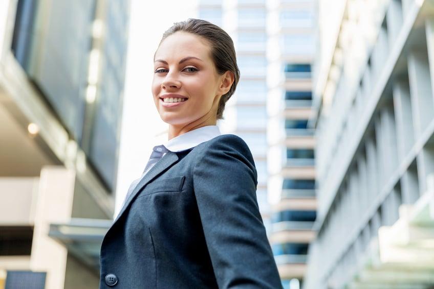 Eine Geschäftsfrau in einer blauen Jecketjacke und hellblauen Hemd steht vor einem großen Bürocenter und lächelt sehr sebstbewusst in die Kamera. Mit ihrer Mimik drückt sia aus, dass sie mit dem Programm der unibee Intsitute, eine gute Gefühlsbalance erreichen konnte und somit positiv in eine gute Zukunft schaut.