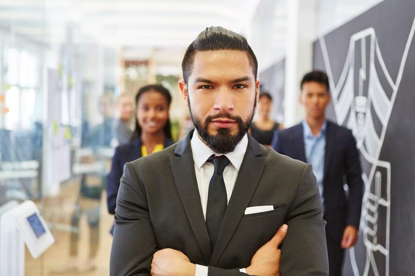 Ein Mann steht in einem Großraumbüro und schaut mit verschränkten Armen direkt in die Kamera. Er strahlt großartiges Selbstbewusstsein aus welches er mit dem Programm der unibee Institute gewonnen hat. Er ist bekleidet mit einem grauen Anzug und grauer Kravatte auf weissen Hemd. Er hat kurze schwarze Haare und trägt einen Vollbart. Im Hintergrund 4 Menschen verschwommen zu sehen, weil der Kamerafokus nur auf den Geschäftsmann gerichtet ist.