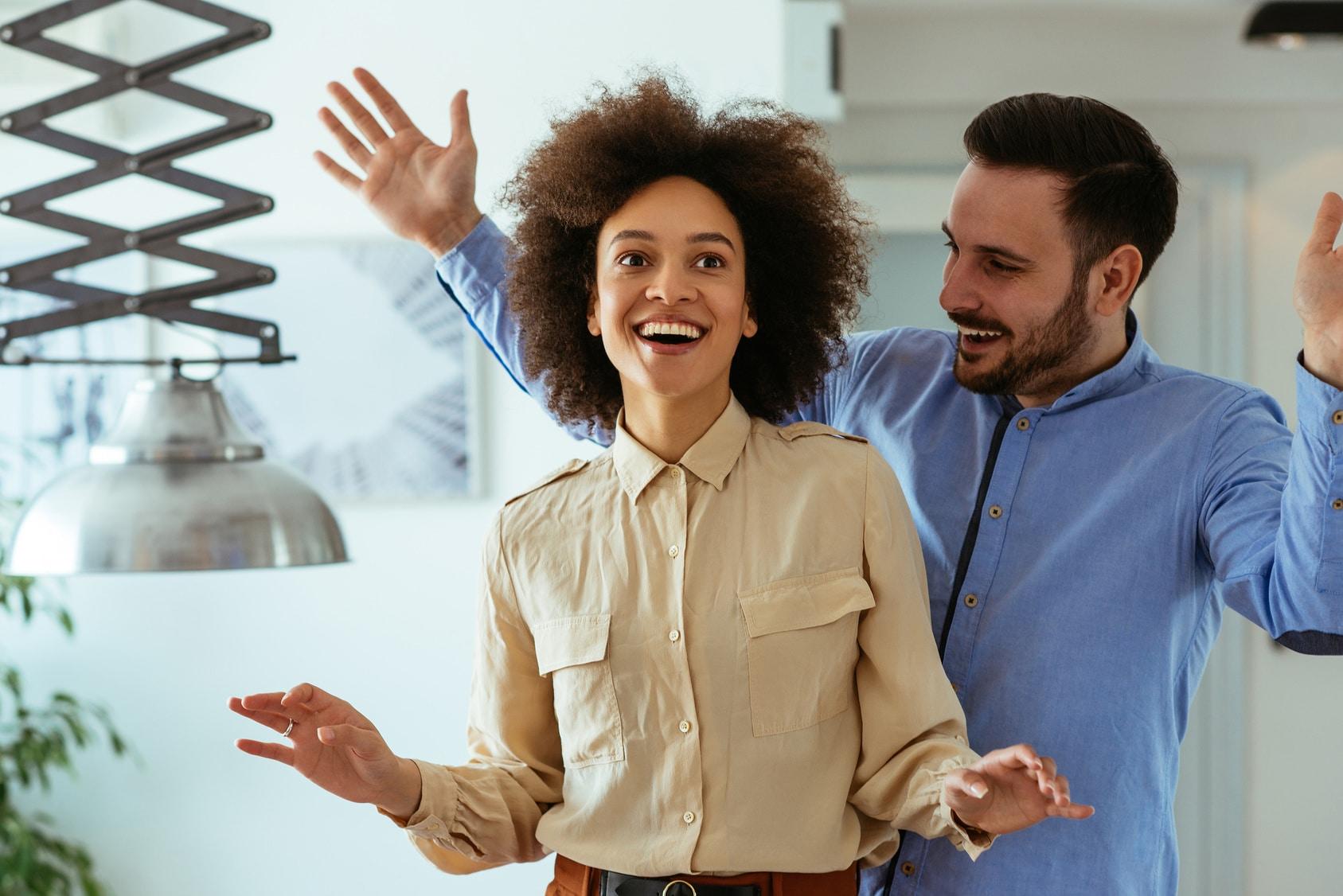 Eine Frau und ein Mann lachen sehr zufrieden miteinander. Mit dem Programm der unibee Institute, konnten beide Personen, ihr Selbstbewusstsein stärken und dauerhaft verankern. Sie hat schwarze gelockte afrikanische Haare und ist bekleidet mit einem hellbraunen Hemd. Der Mann hat kurze schwarze Haare und ist bekleidet mit einem blauen Freizeithemd. Im Hintergrund ist ein Wohnzimmer leicht verschwommen zu sehen.
