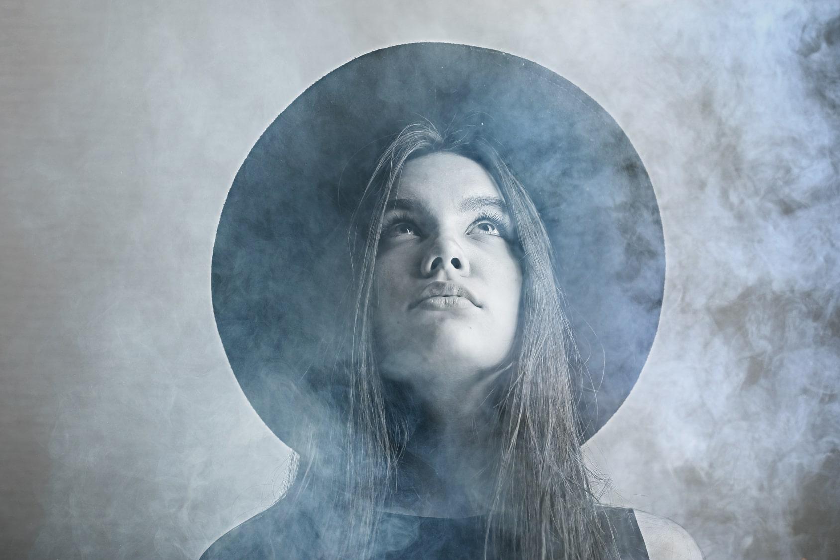 Eine junge Frau steht im Nebel und schaut in die Luft. Ihre Gesichtsmimik zeigt ganz klar, dass sie mit dem Programm der unibee Institute erfolgreich ihr Selbstbewusstsein stärken konnte. Die Frau hat lange braune Haare und einen Schmollmund. Mehr als das Gesicht und der Nebel ist auf diesem Bild nicht zu erkennen.
