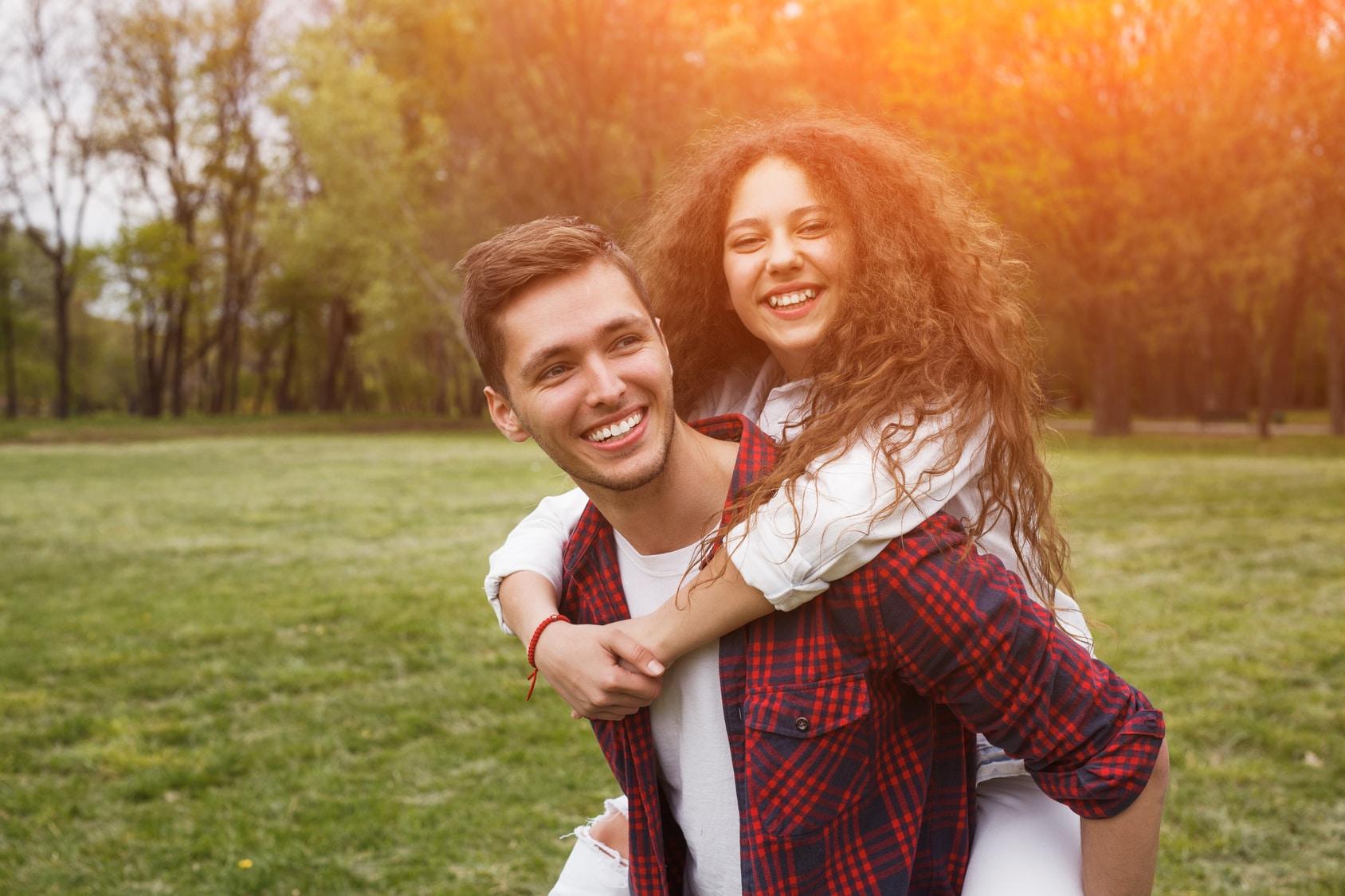 Bruder und Schwester freuen sich und machen einen sehr glücklichen Eindruck. Das Mädchen hat sich auf dem Rücken ihres Bruders eingehängt. Beide strahlen mit Mimik und Gestik ein tolles Selbstbewusstsein aus. Im Hintergrund ist eine grüne Wiese mit einer kleinen Waldlichtung. Sie hat sehr lange braune gelockte Haare und der Junge hat einen Mittellangen Haarschnitt, welcher zur rechten Seite gebürstet ist. Der Junge ist mit einem Karohemd rot / schwarz bekleidet. Das Mädchen trägt eine weisse Windjacke und weisse Jeanshose.