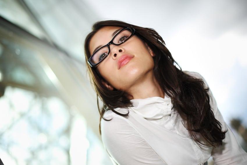Eine Frau im alter von ungefähr 20 Jahre, lange schwarze gelockte Haare mit einer schwarzen Brille, hat einen ausdrucksstarken Blick, welcher echtes Selbstbewusstsein ausstrahlt. Mit dem Programm der unibee Institute hat sie gelernt, eine optimale Balance für ihr Leben zu erreichen. Sie trägt eine weisse Bluse und der Hintergrund ist verschwommen zu sehen, somit ist das Gesicht der Frau sehr deutlich wahrzunehmen.