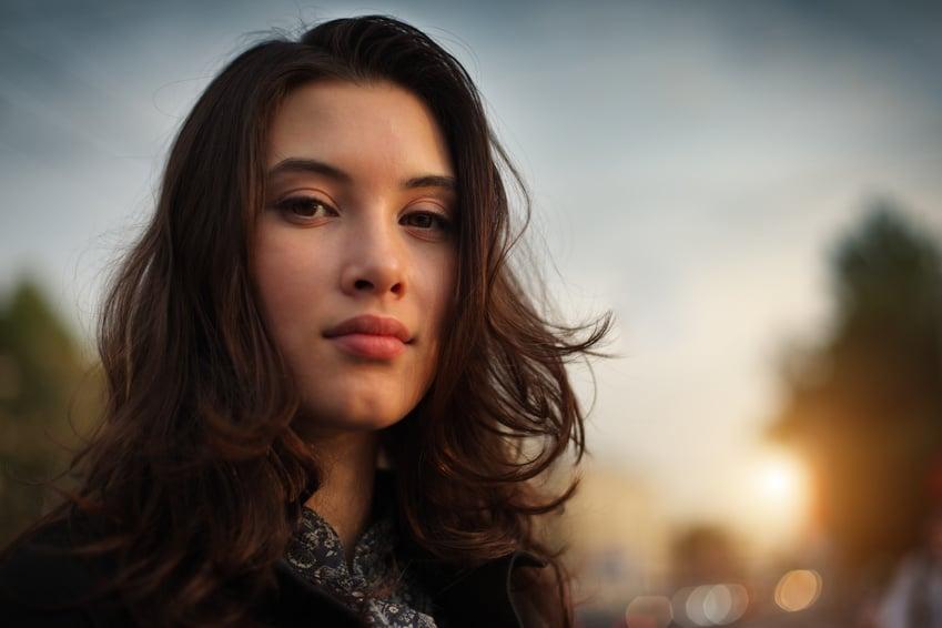 Eine Jung Frau im alter von ungefähr 20 Jahre, steht an einer Strasse und schaut sehr Selbstbewusst mit ihren dunkelbraunen großen Augen in die Kamera. Sie hat lange gelockte braune Haare die im Wind leicht wehen. Sie drückt mit ihrer Mimik ein tolles Gefühl der Balance aus. Frech, sexy, gelassen und elegant.