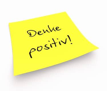 Gelber Notizzettel mit der Aufschrift: Denke positiv!