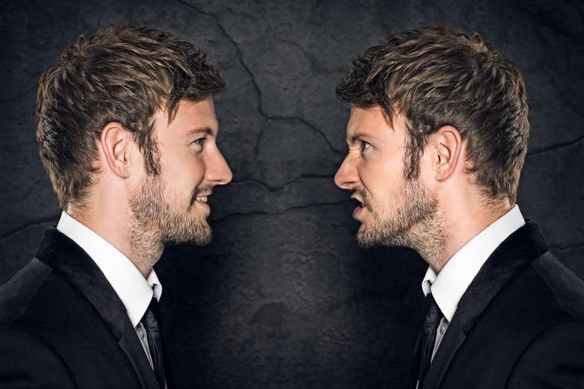 Ein junger Mann steht vor einem Spiegel und schaut sich an. Er macht eine Mimik, sodass er gutes Selbstbewusstsein ausstrahlt. Er hat braune Haare, die nach vorn gebürstet sind, weiterhin hat er einen 3 Tage Bart. Bekleidet ist er mit einem schwarzen Samtanzug und einer schwarzen Kravatte. Er hat ein weißes Hemd darunter an. Der Mann wirkt sehr gepflegt und insgesamt ist das Bild sehr ansprechend. Im Hintergrund ist eine schwarte Wand aus Naturmamor zu sehen.