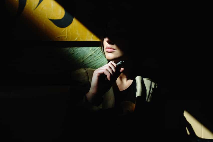 Eine junge Frau sitzt sehr Selbstbewusst auf einem Sofa in einem dunklen Raum. Es ist nur der Mund von der Frau zu erkennen. Das Bild wirkt Mystisch. Im Hintergrund ist eine gelbe Tapete zu erkennen.