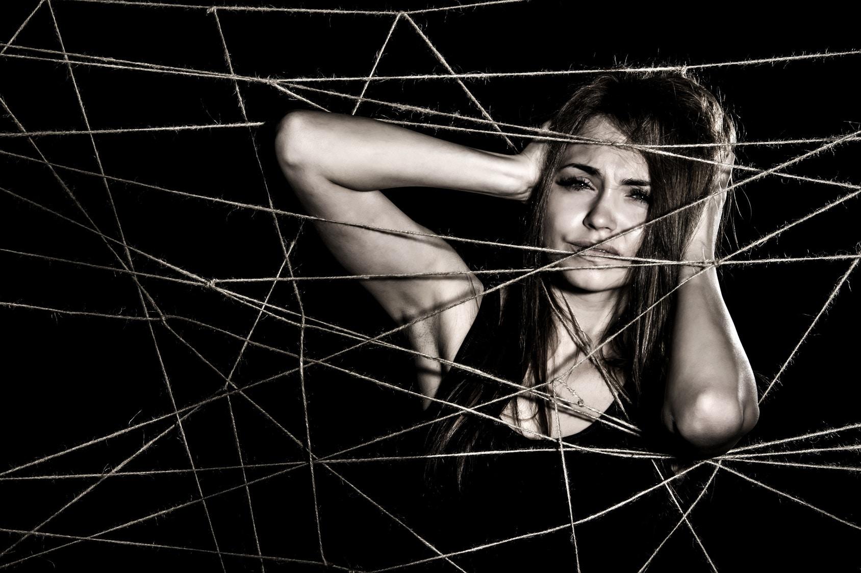 Das Foto ist in schwarz/weiß und zeigt eine junge Frau, die sich gestresst an den Kopf fasst. Sie zeigt damit, dass sie endlich ein gutes Selbstbewusstsein aufbauen konnte. Vor Ihr ist ein Spinnennetz tz sehen, welches sie jetzt nicht mehr stört. Sie hat lange dunkle Haare und ist ekleidet mit einem schwarzen trägerlosen T-shirt.