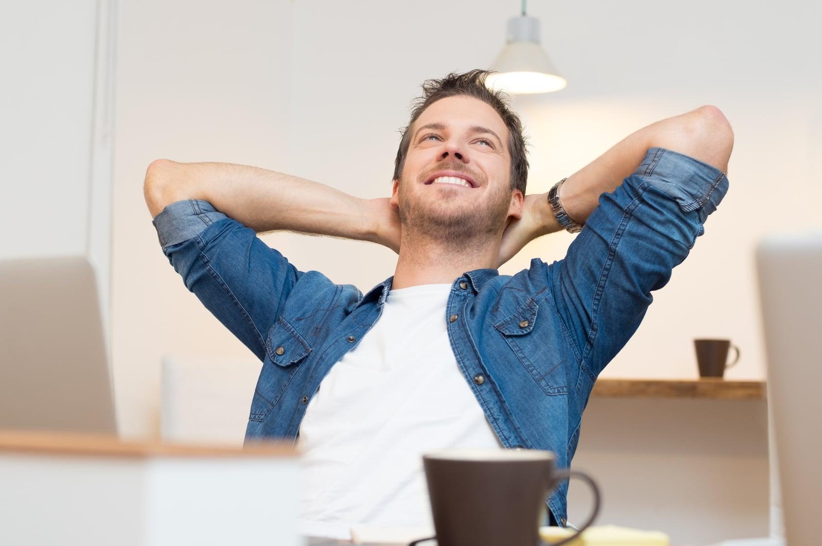 Ein Mann sitzt auf einem Stuhl, hat beide Arme hinter dem Kopf verschränkt und ist nach hinten gelehnt. Er lächelt dabei und zeigt mit seiner Gestik und Mimik, dass er ein starkes Selbstbewusstsein besitzt und dieses auch auslebt. Er hat kurze braune Haare, einen 3 Tage Bart und ist bekleidet mit einem bleuen Jeanshemd und weissen T-shirt. Im Vordergrund ist eine braune Tasse zu sehen und der Hintergrund ist schlicht weiss gehalten.