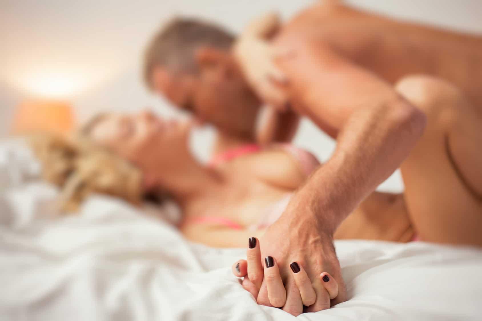Ein Paar liegt im Bett. Der Mann liegt auf der Frau und küsst sie am Hals. Beide strahlen durch die Mimik und Gestik Selsbtbewusstsein aus. Die Frau hat lange blunde Haare und der Mann kurze graue Haare. Die Frau hat schwarz lackierte Fingernägel.