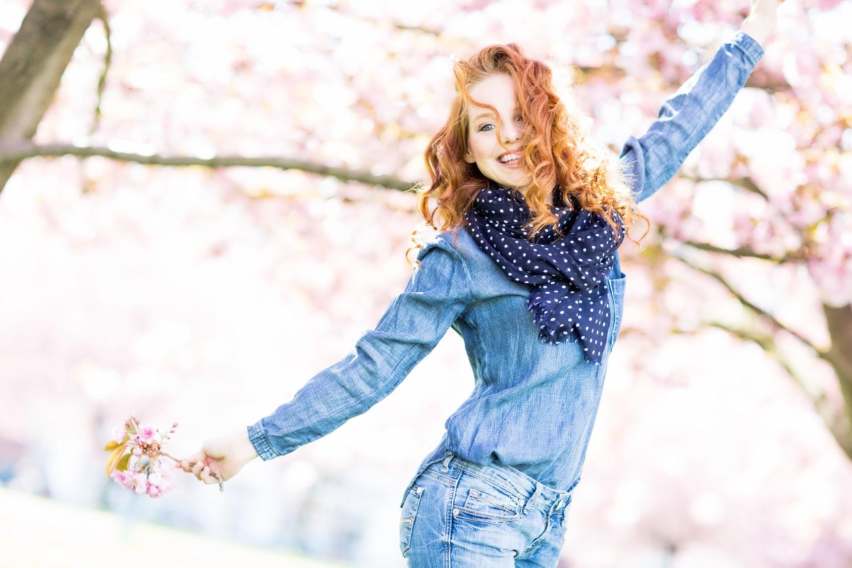 Ein junges Mädchen mit langen und lockig roten Haaren breitet die Arme aus und möchte damit zeigen, dass sie das Selbstbewusstsein stärken konnte und sehr opsitiv in eine erfolgreiche Zukunft blickt. Sie trägt ein Hosenanzug aus bleuer Jeans und um den Hals trägt Sie ein dunkelblaues Halstuch mit weissen Punkten. Im Hintergrund ist ein lila blühender Fliederbaum zu sehen und der Himmel ist Wolkenlos.