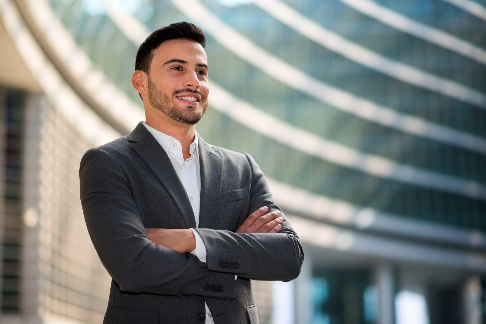 Ein junger Man mit kurzen schwarzen Haaren steht mit verschränkten Armen und erhobenem Kopf vor einem großen Bürogebäude. Er strahlt mit seiner Mimik ein starkes Selbstbewusstsein aus. Er ist bekleidet mit einem grauen Anzug und weissem Hemd.