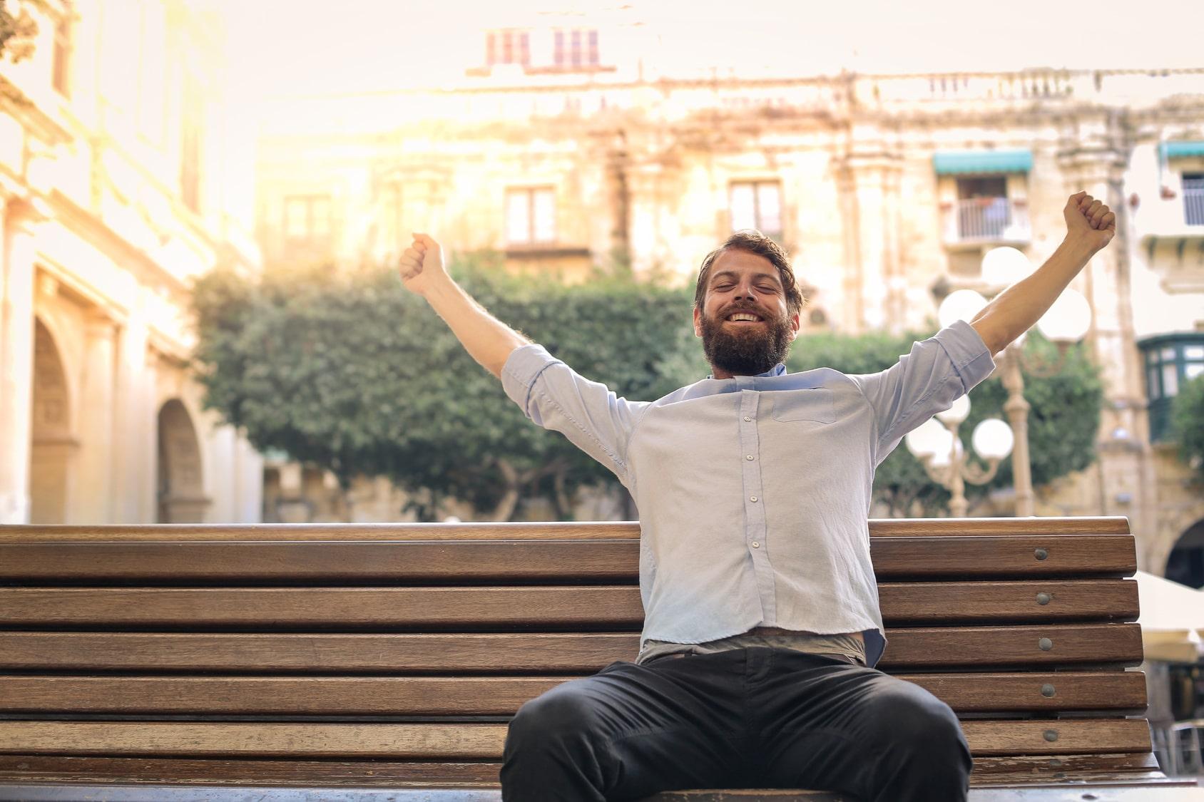 Ein junger Mann mit Vollbart und kurzen braunen Haaren, sitzt auf einer Bank an einer Strasse vor einem alten großen Gebäude. Er hebt beide Arme nach oben und ballt seine Hände zu einer Faust und lächelt dabei sehr glücklich. Er zeigt mit seiner Gestik und Gesichtsmimik, dass er mit dem Programm der unibee Institute, sein Selbstbewusstsein ausserordentlich gut aufbauen konnte. Er ist bekleidet mit einem blauen Hemd und einer schwarzen Jeanshose. Es ist ein sonniger Tag.