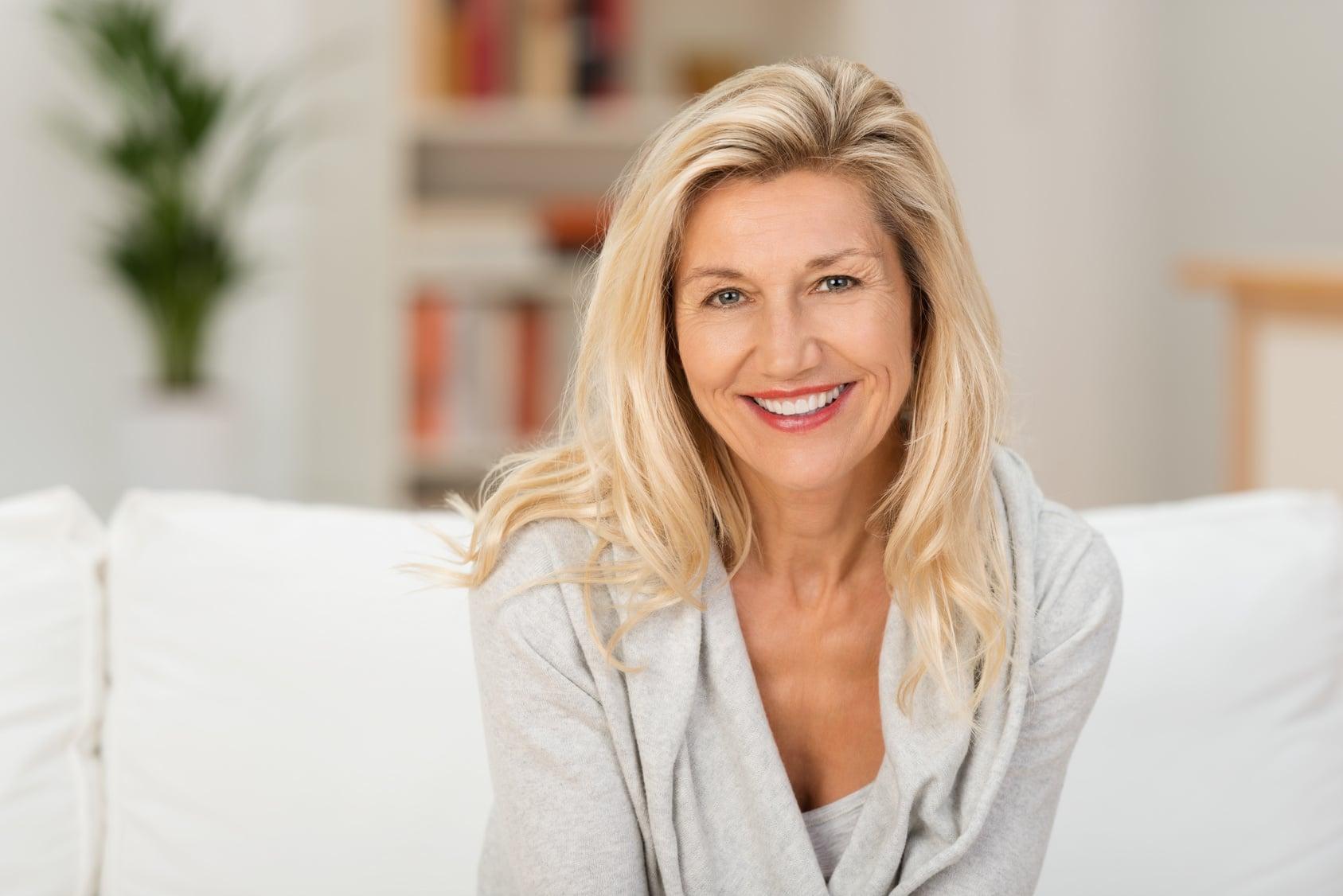 Eine ältere Frau ungefähr 50 Jahre mit langen blonden Haaren lächelt zufrieden und beugt sich leicht nach vorn zur Kamera hin. Mit ihrer Mimik strahlt sie gute Balance und gutes, stabiles Selbstbewusstsein aus. Sie sitzt auf einem weissen Sofa welches in einem Wohnzimmer steht. Im Hintergrund ist ein Bücherregal mit orangenen Büchern zu sehen und links daneben steht eine große grüne Zimmerpflanze.