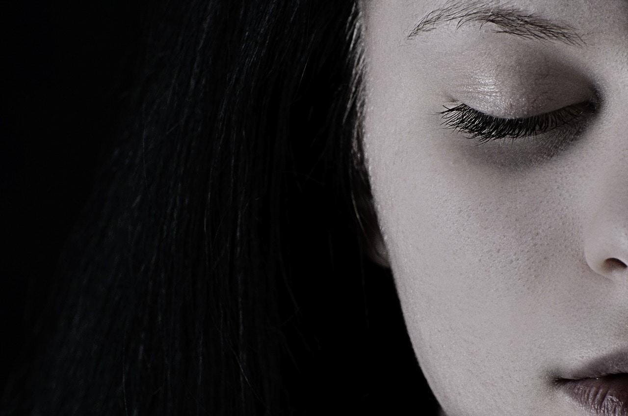Eine Bild schwarz/weiss zeigt ein Gesicht einer Frau welches zur Hälfte am rechten Bildrand abgeschnitten ist. Die Augen sind geschlossen. Das Bild signalisiert eine Sitzung in bei einer Psychotherapie zum Selbstbewusstsein stärken.