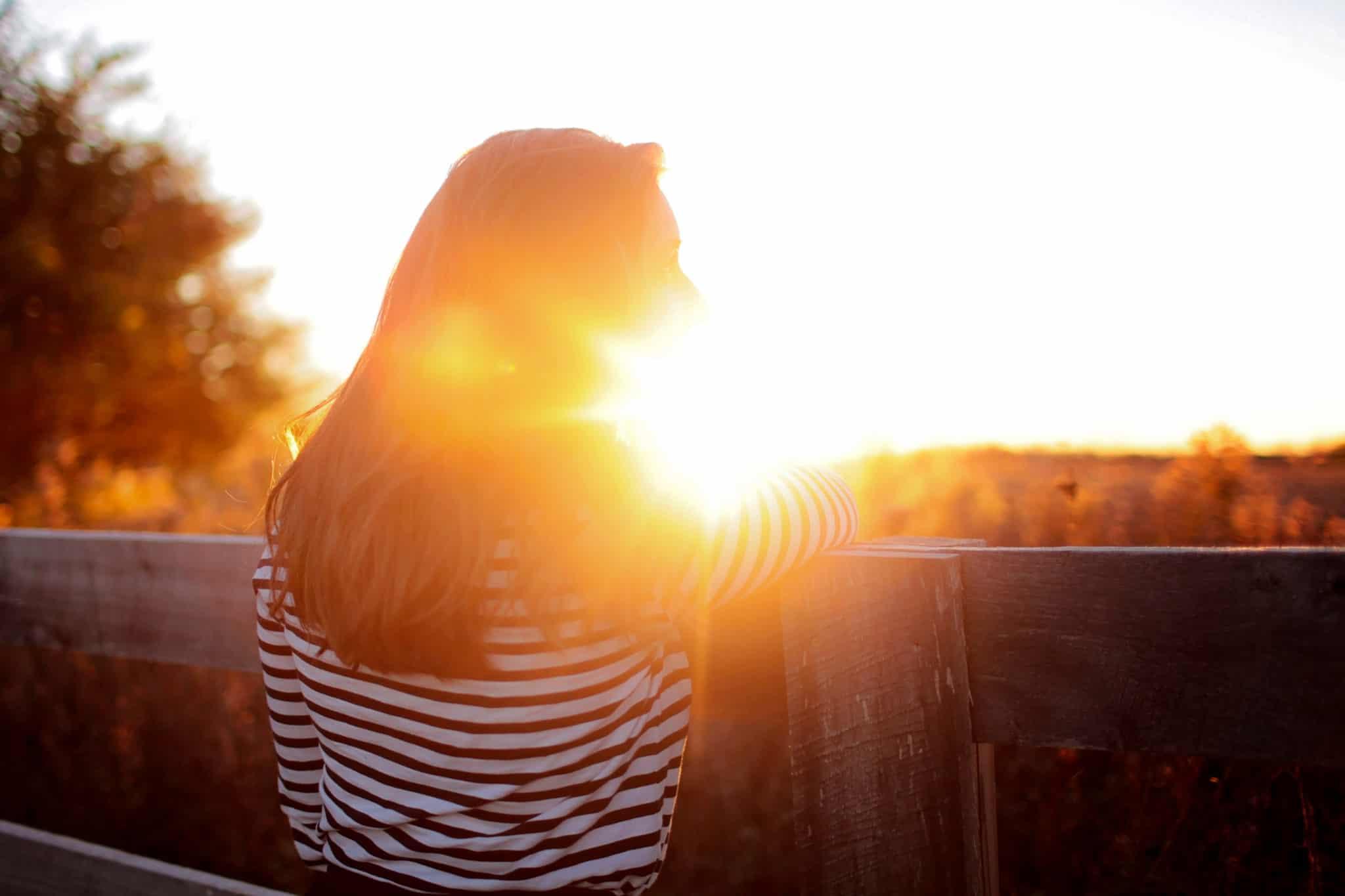 Eine Frau steht auf einer Terasse und sieht einen leuchtend hellen Sonnenuntergang zu. Auf dem Foto ist die Frau von hinten zu sehen und sie ist bekleidet mit einem weiss/blau getreiften Pullover. Sie hat lange braune Haare. Sie versucht durch den Blick in den Sonnenuntergang um ihre kreisenden Gedanken loszulassen um ihr Selbstbewusstsein zu spüren und zu stärken.