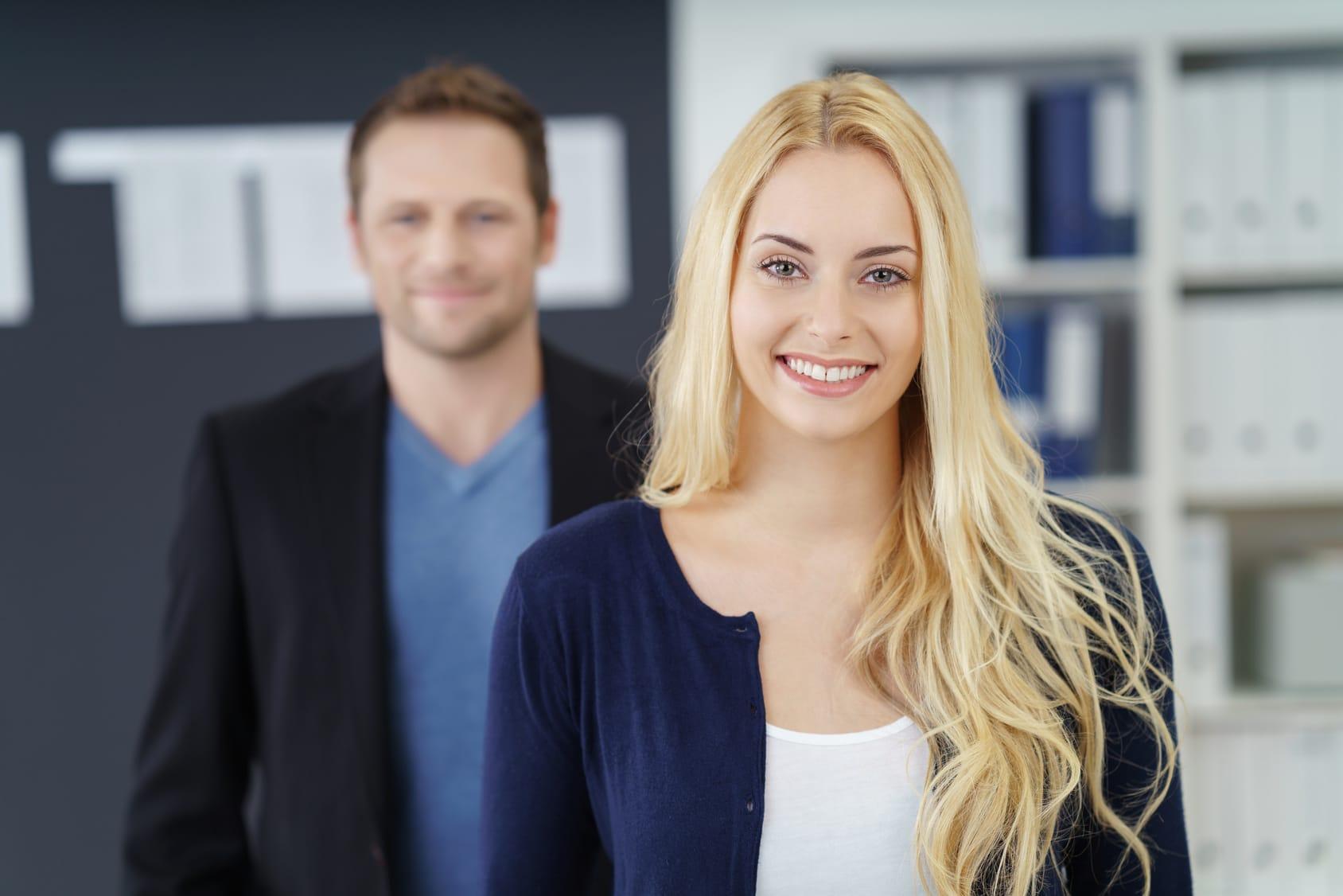 Eine junge Frau mit sehr langen hellblonden Haaren lächelt sehr selbstbewusst. Mit dem Programm der unibee Institute, konnte Sie wieder lernen, echte Balance im Leben wieder zu erreichen. Sie trägt ein weisses T-shirt und eine blaue Sommerjacke. Im Hintergrund steht ein Mann, welcher aber nur verschwommen zu sehen ist. Beide stehen in einem Büro mit einem großen Bücherregal im Hintergrund.
