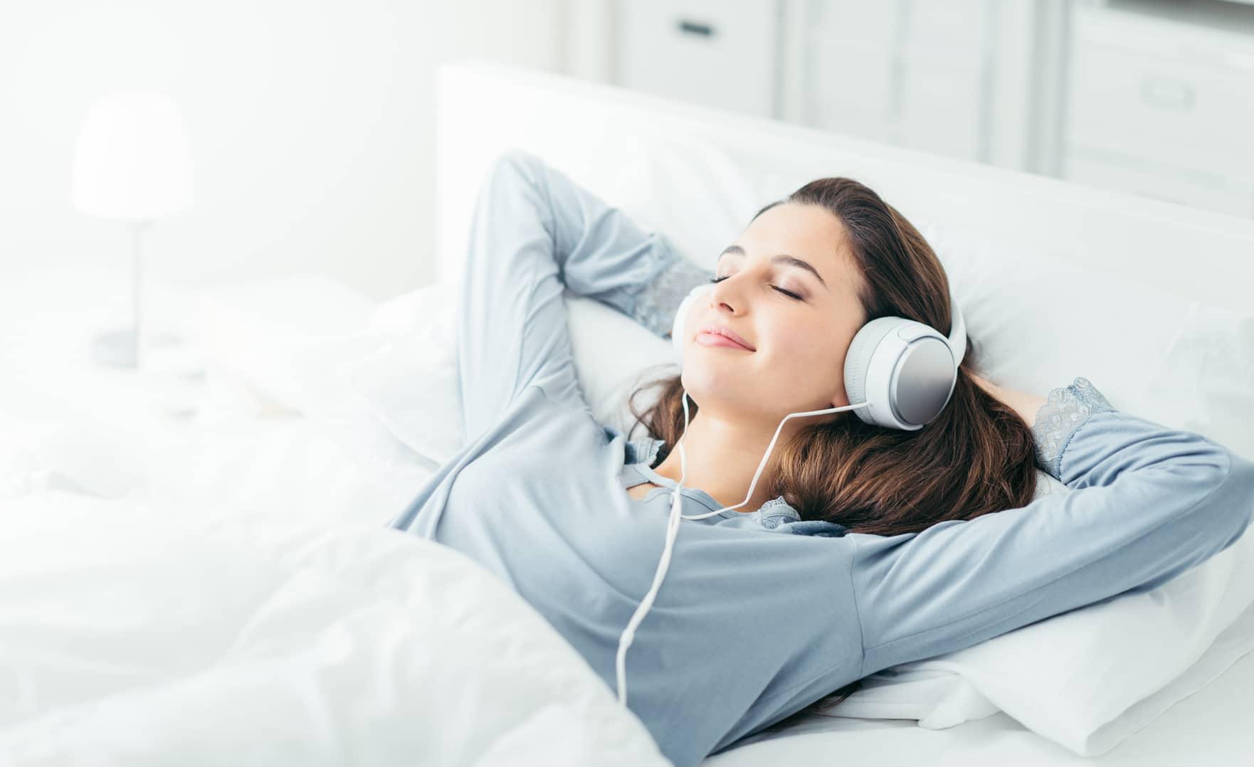 Erklärbild: Junge Frau liegt im Bett und hört sich eine Hypnose zum Aggressionen abzubauen.