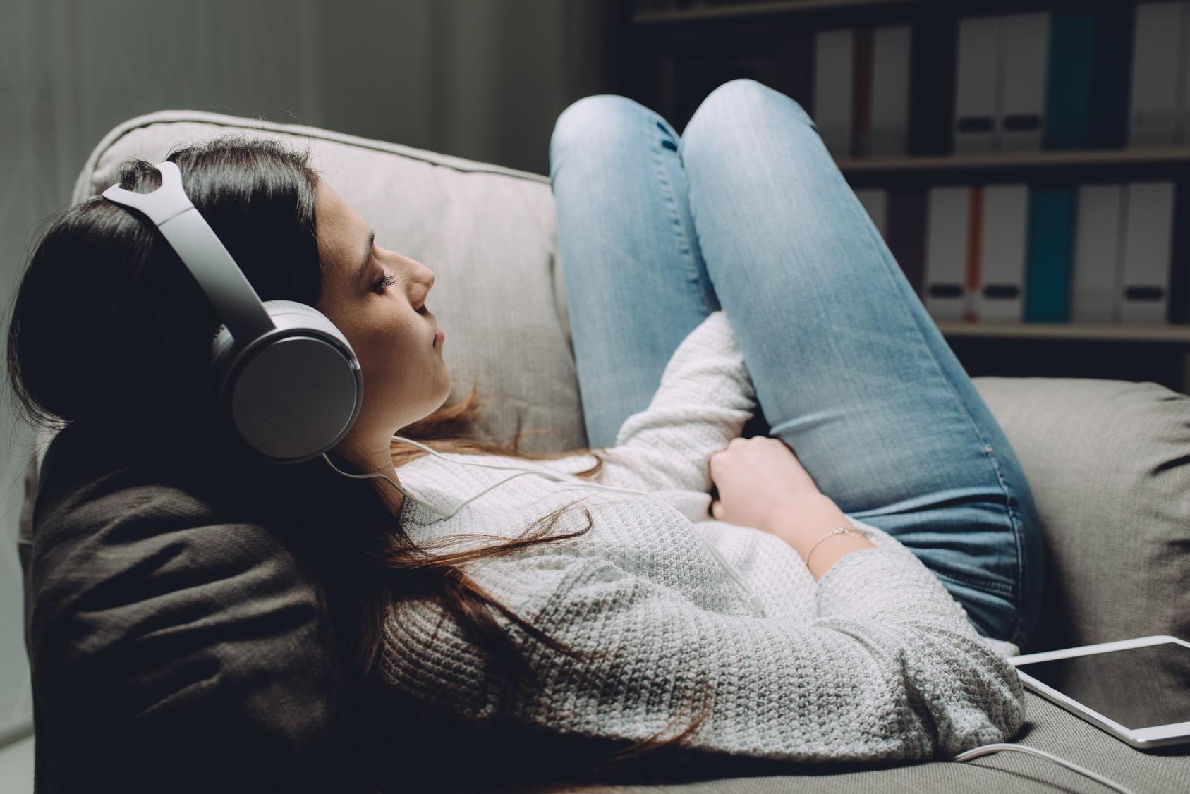 Eine junge Frau liegt entspannt im Sofa und hört eine Hypnose CD zum Selbstbewusstsein stärken von den unibee Instituten. Sie hat lange schwarze Haare und große silberne Kopfhörer auf. Bekleidet ist sie mit einem grauen Pullover und einer hellblauen klassischen Jeanshode. Im Hintergrund ist ein Bücherregal zu sehen, worin sich viele weisse Aktenordner befinden.