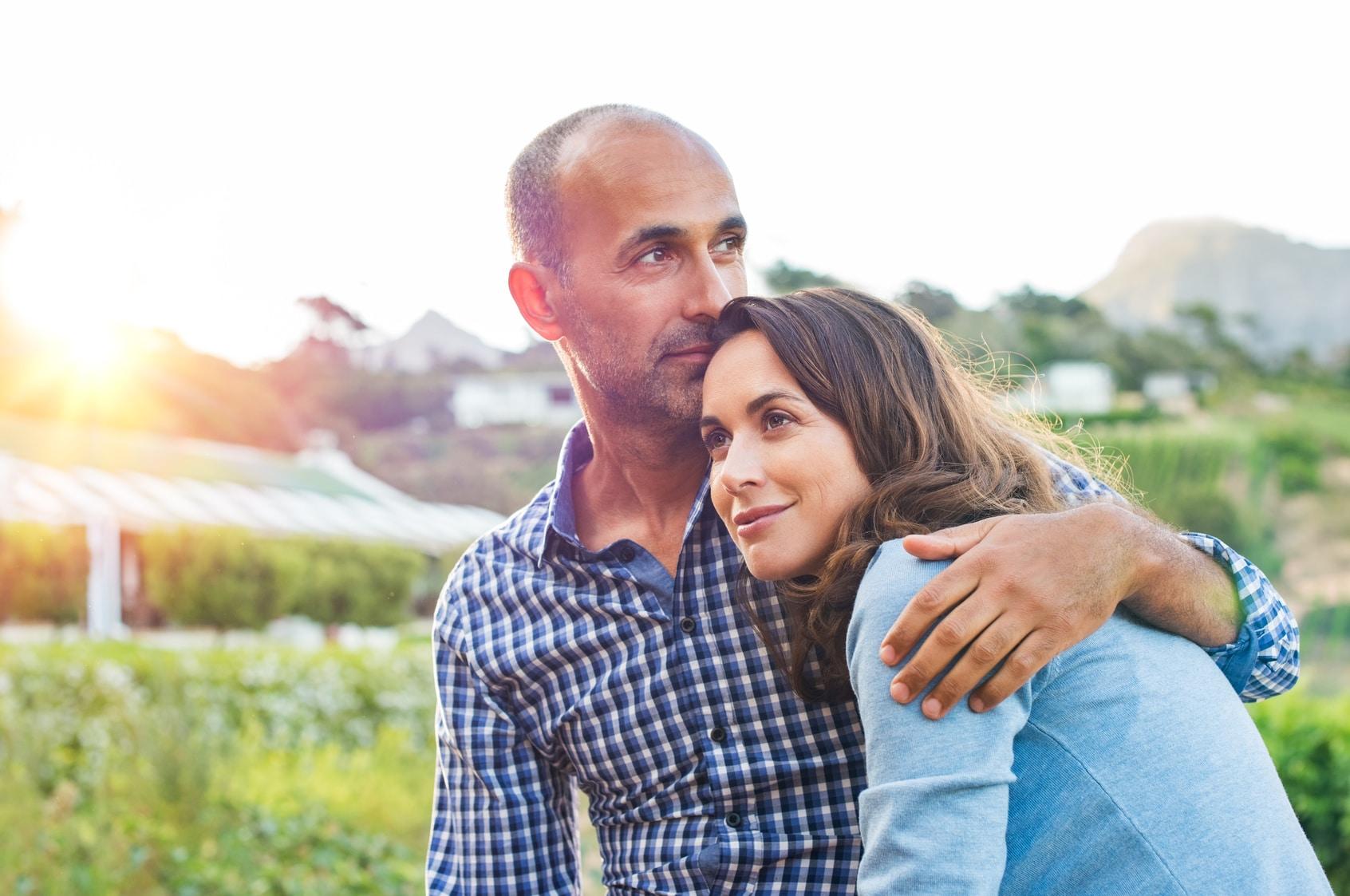Ein Paar mitleren Alters steht auf einer grünen Wiese. Der Mann hält seine Frau im Arm und lächeln leicht und wirken entspannt. Sie zeigen mit ihrer Mimik und Gestik Gefühle der Harmonie. Ser Mann zeigt deutlich ein Selbstbewusstses auftreten, so als würde er seine Frau jederzeit beschützen können. Der Mann hat keine Haare und die Frau hat lange dunkelbraune gewellte Haare. Sie ist mit einem hellblauen Pullover bekleidet und er trägt ein blau/weiss kariertes Freizeithemd.