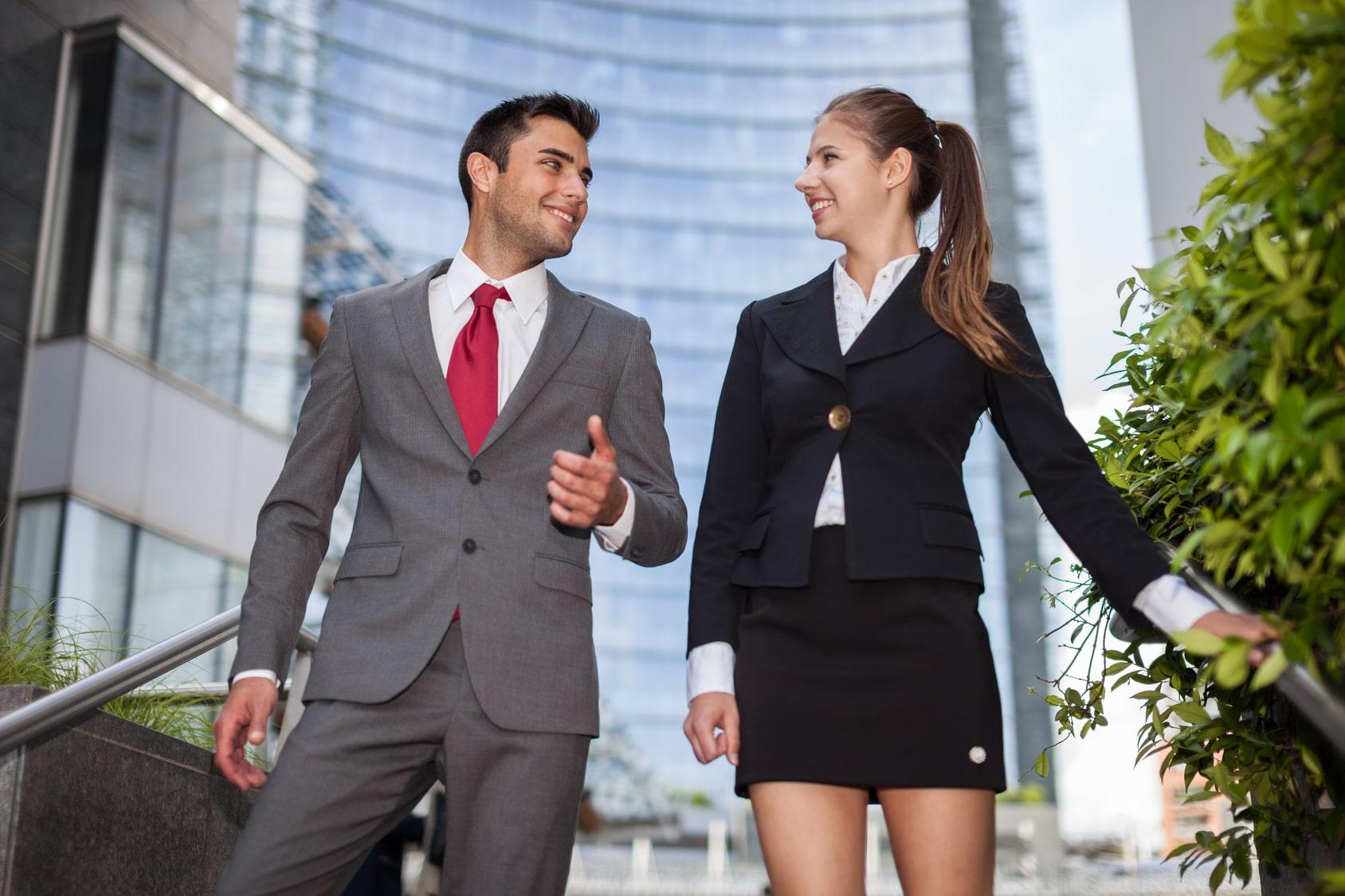 Ein Mann und eine Frau laufen eine Treppe hinunter und unterhalten sich dabei. Beide sind Arbeitskollegen und strahlen ein sehr starkes selbstbewusstsein aus. Er ist bekleidet mit einem hellgrauen Anzug, weisses Hemd und roter Kravatte und die Frau trägt eine schwarze Jacketjacke mit einem passend kurzen schwarzen Rock in Kniehöhe. Im Hintergrund ist ein Hochhaus mit einer Glasfassade zu sehen.