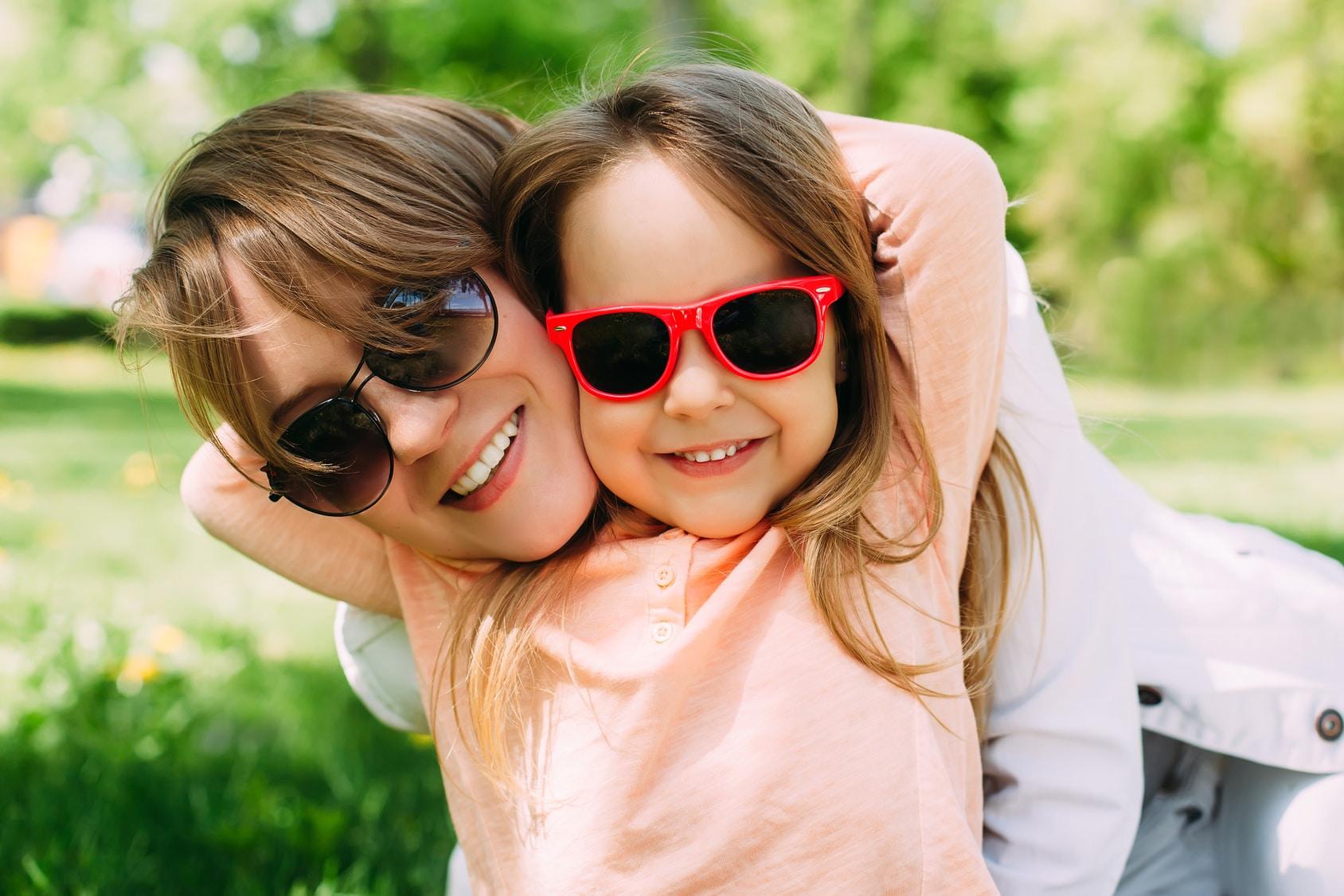 Eine Mutter mit ihrer Tochter strahlen lässig in die Kamera. Beide haben das Programm der unibee Institute zum Selbstbewusstsein stärken genutzt um eine gute Lebensbalance zu bekommen. Mit ihrer Mimik strahlen beide ein gutes Lebensgefühl aus. Beide tragen eine Sonnenbrille und haben lange hellbraune Haare. Bekleidet ist die Frau mit einer weissen Jeansjacke und das Mädchen trägt einen hellrosa Pullover. Im Hintergrund ist ein Naturpark mit vielen blühenden Pflanzen zu sehen.