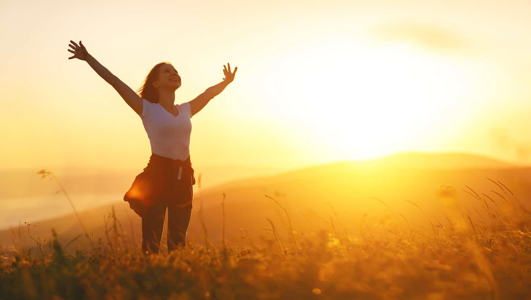 Eine junge Frau steht auf einer großen Wiese im Morgennebel und streckt beide Arme in den Himmel. Mit dieser Gestik zeigt sie deutlich, dass sie mit dem Programm der unibee Institute, ihr Selbstbewusstsein zurück erlangen konnte und positiv in die Zukunft schaut. Im Hintergrund sind 2 große Berge zu sehen. Bekleidet ist die Frau mit einem weissen T-shirt, blaue Jeanshode und hat eine rote Jacke um die Hüfte gebunden. Die langen braunen Haare wehen im Wind.